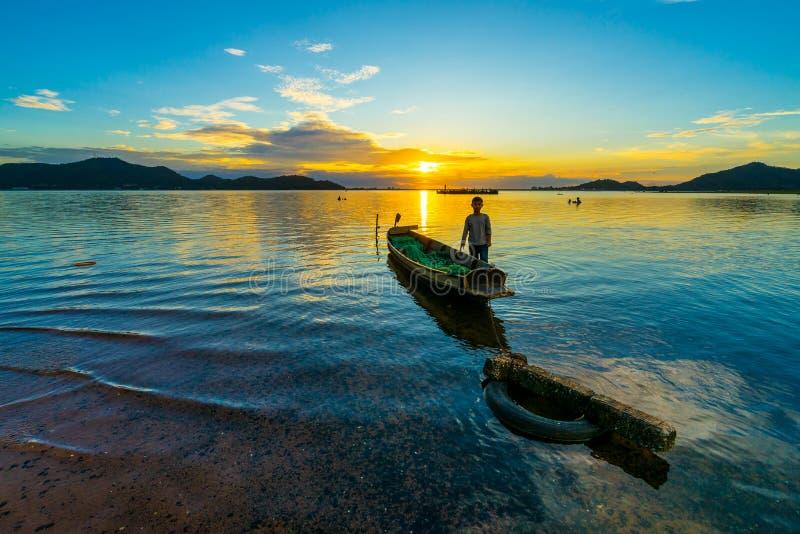 Fiskefartyg med barnpojke vid solnedgången i Bang phra reseroir, sriracha chon buri, Thailand royaltyfri bild