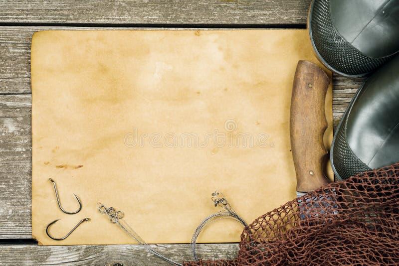 Fiskekugghjul - fiske, blyertspenna, krokar, kängor, träbakgrund royaltyfria bilder