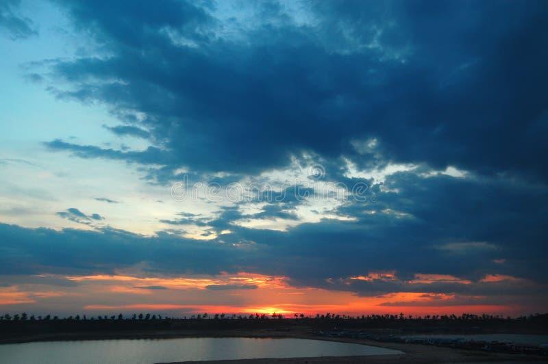 Fiskeläge på sjön med molnig solnedgång royaltyfria foton