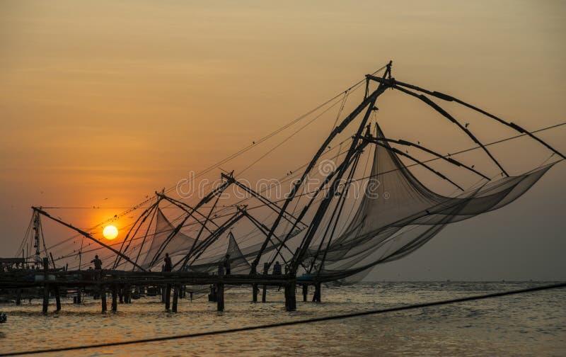 Fiskenät vid solnedgång i Cochin, Indien arkivbild