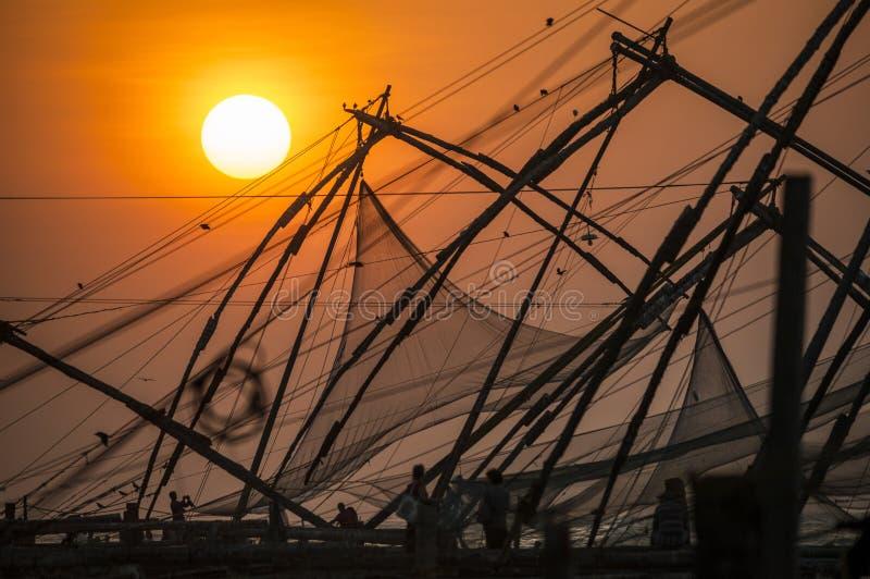 Fiskenät vid solnedgång i Cochin, Indien fotografering för bildbyråer