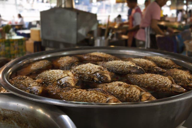 Fisken kokade med kryddor och svart rimmad såssoppa i eldfast form i marknadsbakgrund royaltyfri foto
