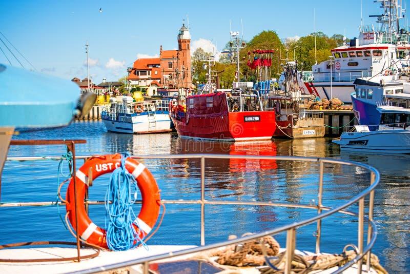 Fiskeport av Ustka, Polen med den gamla fyren royaltyfria bilder