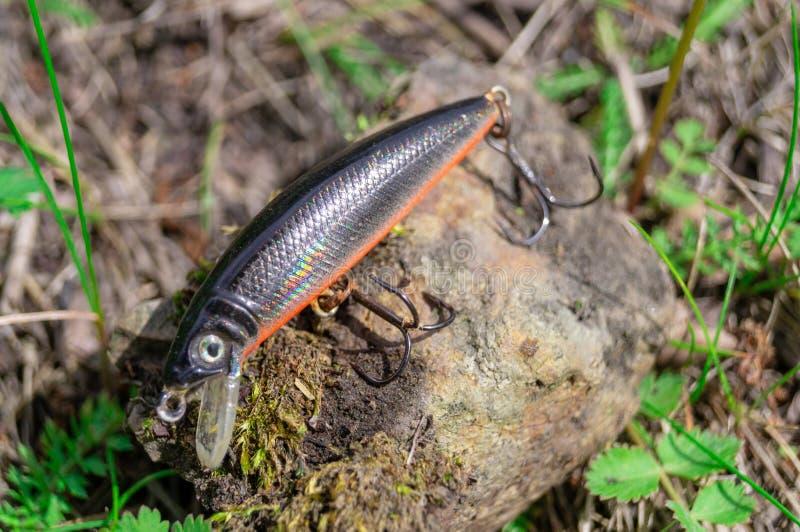 Fisketillbeh?r Struntsaker och lockar att ligga på en sten med en skogbakgrund arkivbilder