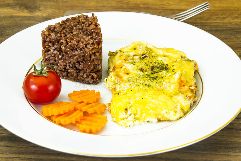 Fiskfilé i krämig sås med grönsaker, röda ris royaltyfria foton