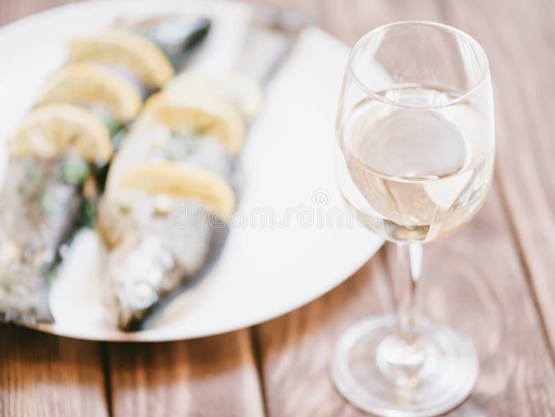 Fiskforellmaträtt och exponeringsglas av vitt vin royaltyfri fotografi