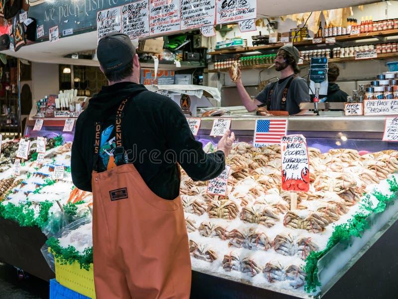 Fiskhandlaren fångar den Dungeness krabban på den offentliga marknaden, Seattle royaltyfri bild