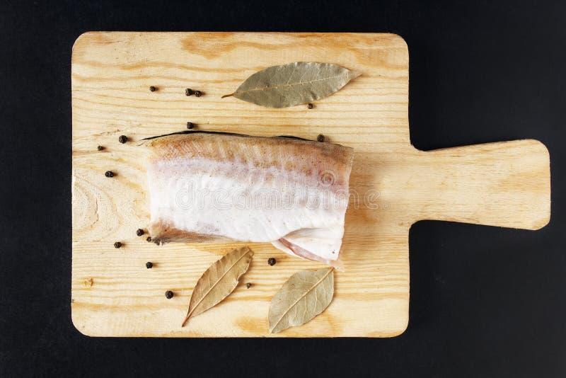Fiskkött med kryddan på skärbräda Pepparärtor och lagerblad Bästa sikt på svart bakgrund royaltyfria foton