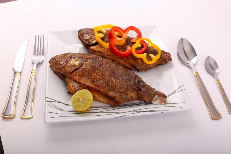Fiskmål med citronen och skivor av spansk peppar royaltyfria foton