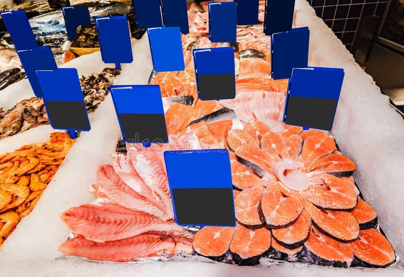 Fiskmat med massor av etiketter i marknaden arkivbild