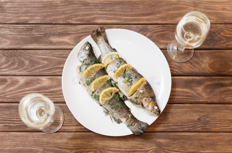 Fiskmaträtt med exponeringsglas av vin arkivfoto