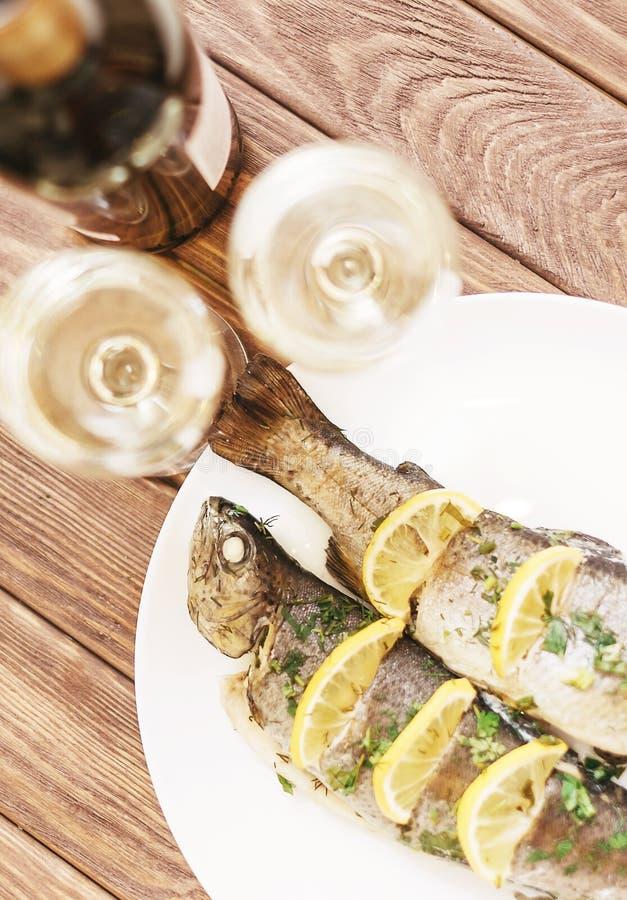 Fiskmaträtt på en platta och exponeringsglas av vitt vin royaltyfri foto