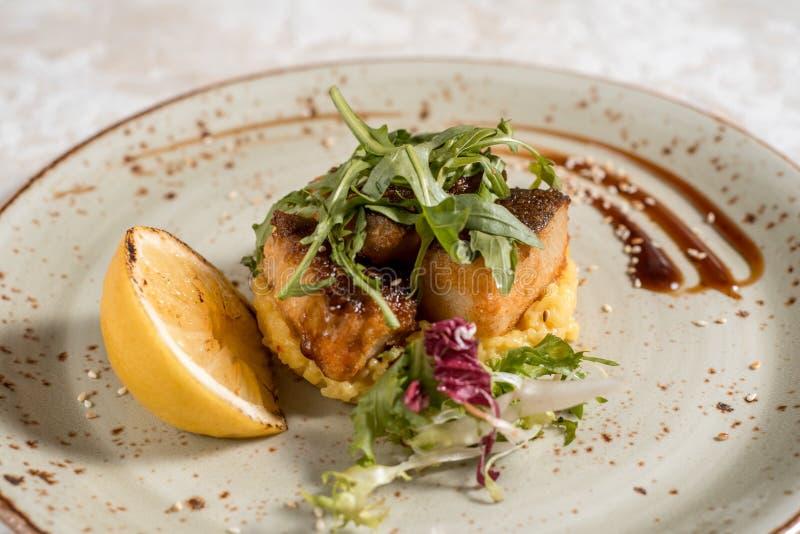 Fiskmatr?tt - stekt fiskfil? med stekte potatisar och gr?nsaker arkivfoton