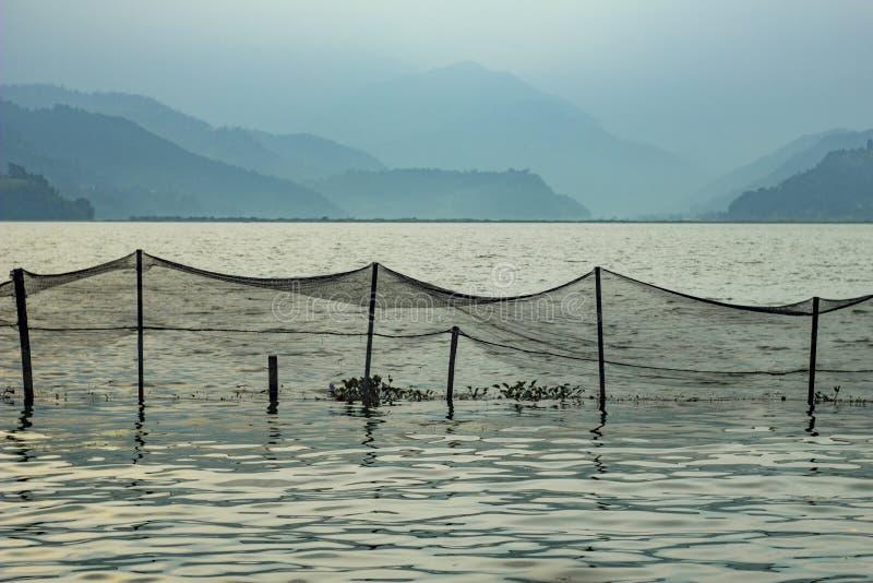 Fisknät över sjövattnet på bakgrunden av oskarpa berg i dimman i aftonen royaltyfri fotografi