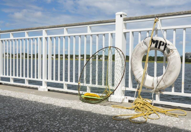 Fisknät- och livPreserver som hängs på pir med det gula repet royaltyfria foton