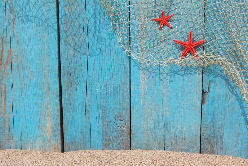 Fisknät och röda sjöstjärnor mot en gammal träbakgrund royaltyfria foton