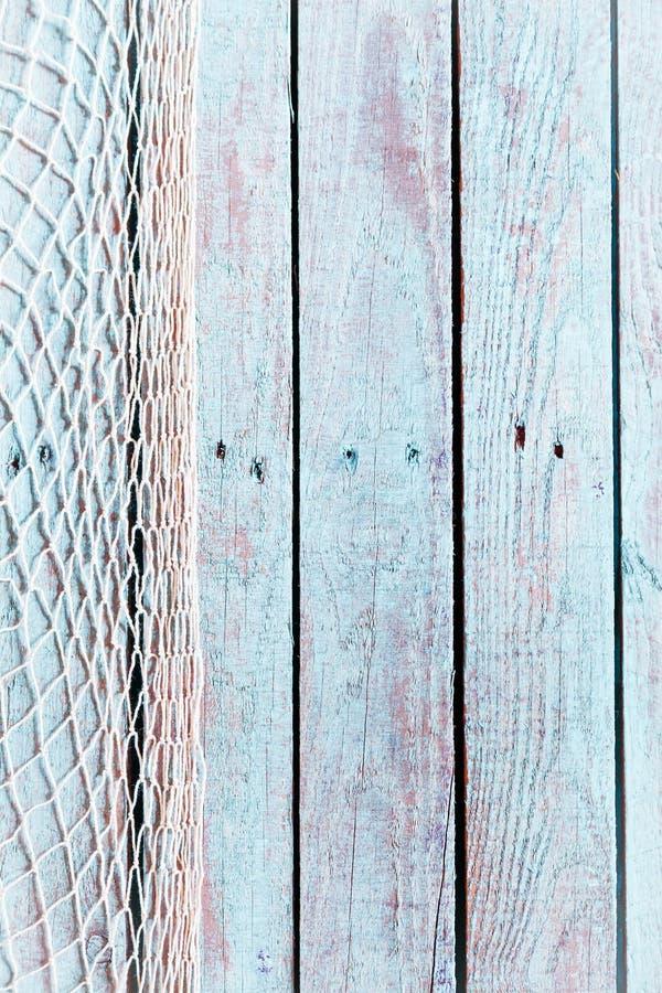 Fisknät på gamla lantliga blåa träbräden royaltyfri bild