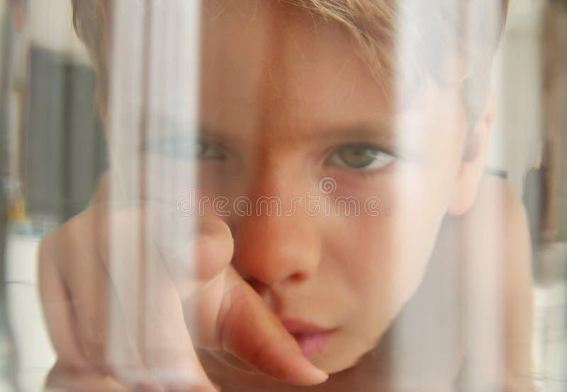 Fiskperspektiv: se en unge som trycker på akvariumexponeringsglaset royaltyfria bilder