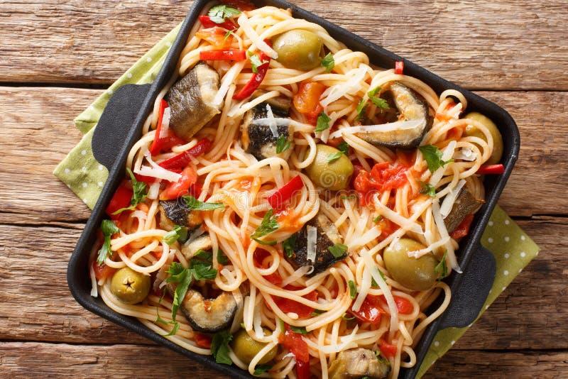 Fiskspagetti med stekt ål-, oliv-, peppar- och tomatsåsnärbild på en platta horisontalb?sta sikt royaltyfria bilder