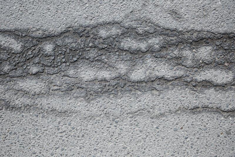 Fissures humides sur l'asphalte sec image libre de droits