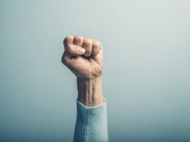 Fist in the air. A clenched male fist is up in the air stock photo