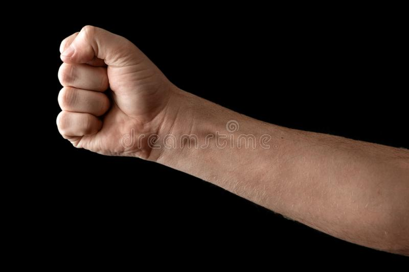 Fist isolated on black background. A strong man raised his fist on a black background, power, protest, fist ready for battle stock photography