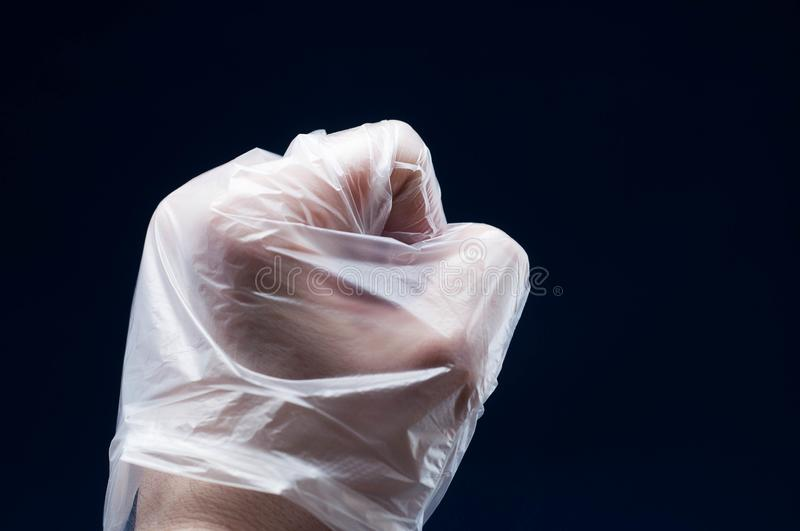 Hand signs in polyethylene gloves on a dark background with good lighting stock photo