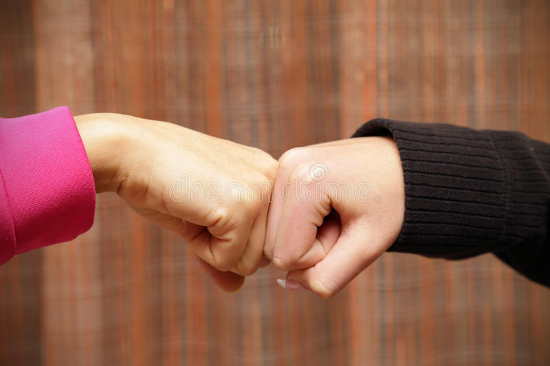 Fist to fist. A salute alternate between two women stock image