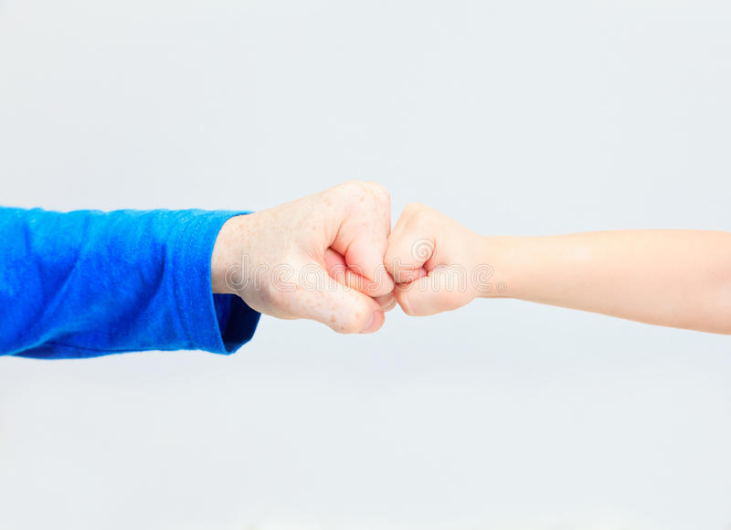 Fists of an adult and a child on white. Family conflict stock photo