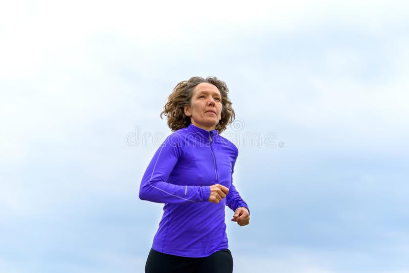 Fit active woman running against a cloudy sky. Fit active woman running in a semi-urban environment in a low angle view against a cloudy sky in a healthy royalty free stock photography