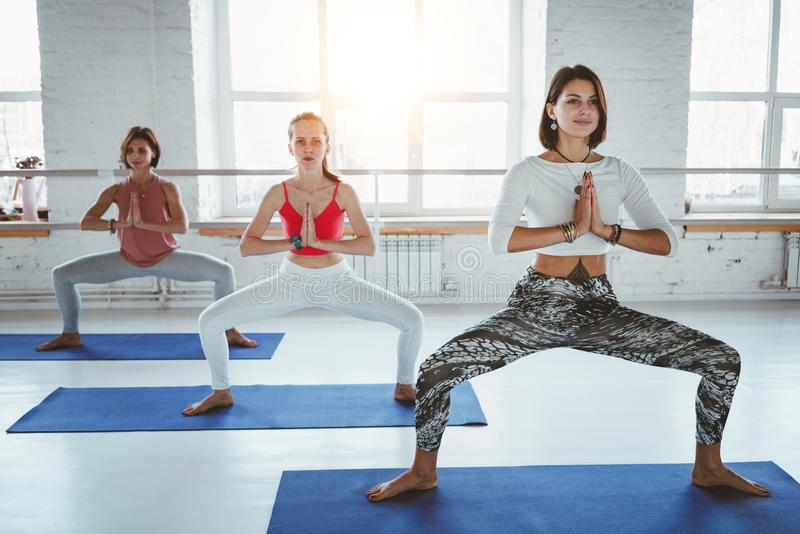 Fit adult women practicing yoga poses in fitness class. Group of healthy strong female doing fit exercises in white gym. Health care and lifestyle stock photo