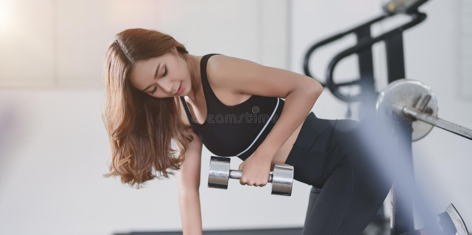 Fit asian athletic woman lifting weights inside home gym royalty free stock image