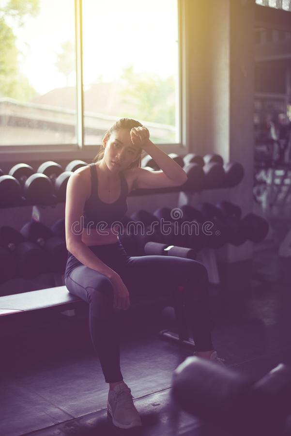 Fit asian woman sitting and relax after the training session,Concept healthy and lifestyle,Female taking a break after exercise an royalty free stock images