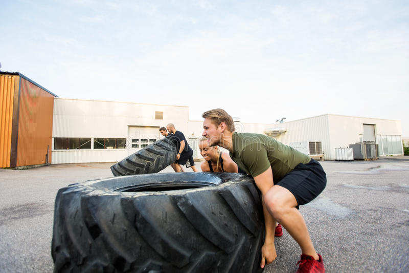 Fit Athletes Doing Tire-Flip Exercise. Fit male and female athletes doing tire-flip exercise outdoors royalty free stock photos