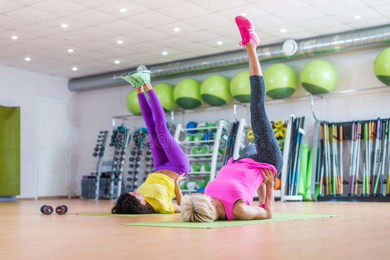 Fit athletic female doing single leg bridge exercise on mats at group classes in gym against bright sport equipment royalty free stock image