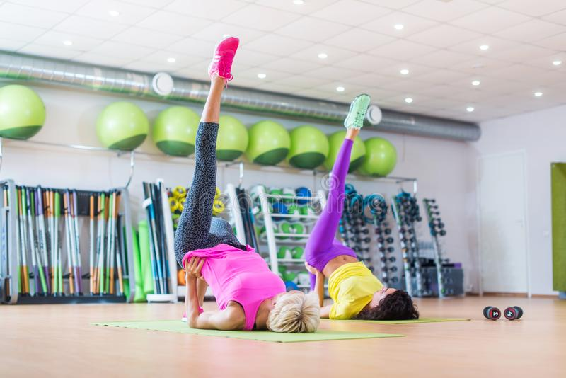 Fit athletic female doing single leg bridge exercise on mats at group classes in gym against bright sport equipment.  stock images