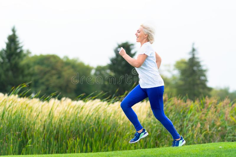 Fit athletic mature woman running alongside reeds royalty free stock photo