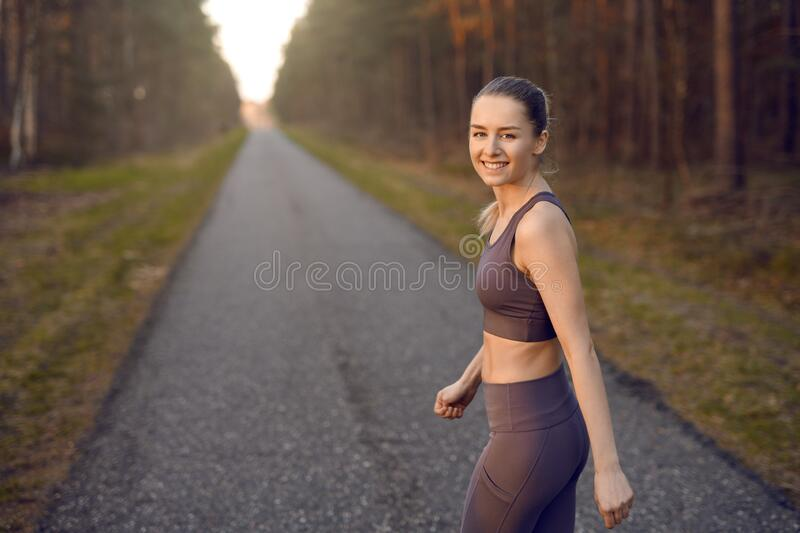 Fit athletic young woman out jogging at sunrise stock images
