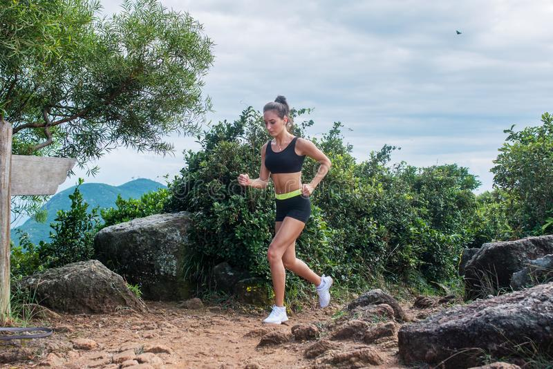 Fit athletic young woman running on dirty rocky path in mountains in summer. stock photos