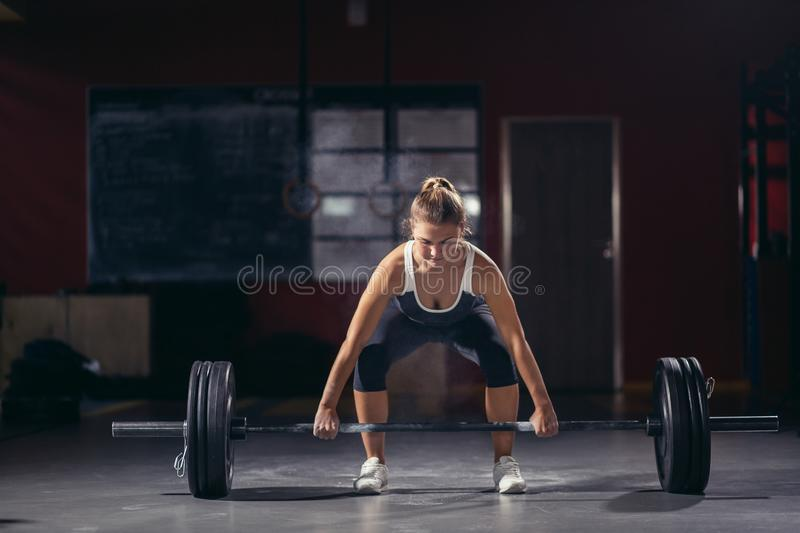 Female holding a barbell in her hands. royalty free stock photography