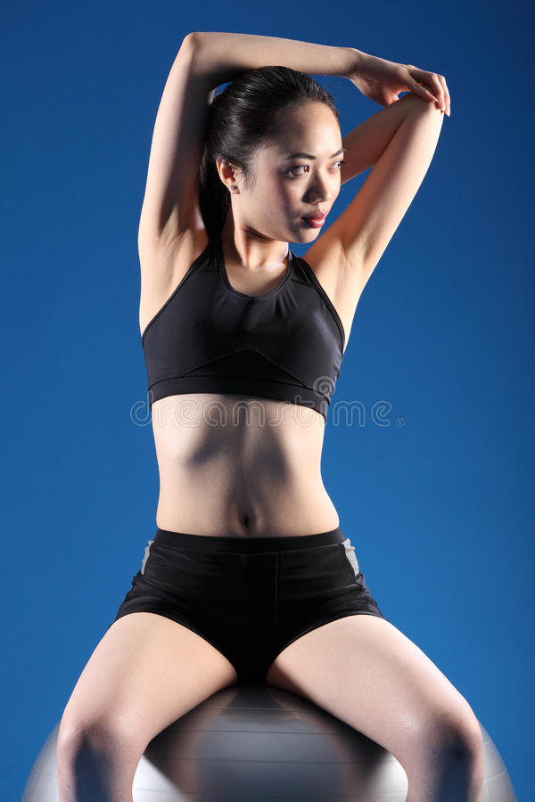 Fit beautiful asian woman warm up stretch exercise. Concentrating on balance exercise while doing warm up stretch, a beautiful young asian woman in sitting pose royalty free stock photo