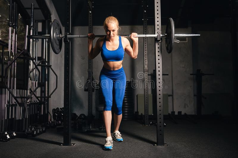 Fit beautiful girl concentrated on training with barbell in gym. Full length photo. sporty, healthy lifestyle, hobby stock image