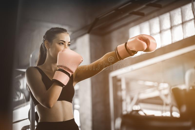 Fit beautiful woman boxer hitting a huge punching bag exercise class in a gym. Boxer woman making direct hit dynamic movement. stock photos