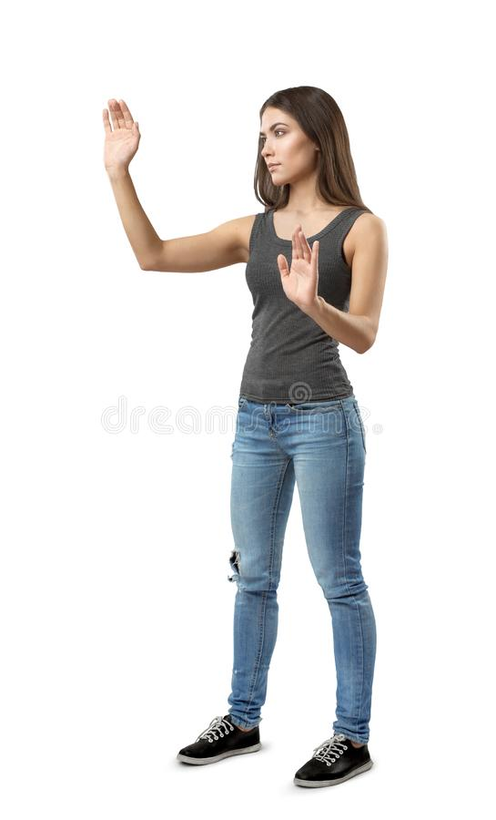 Fit beautiful woman in gray top and blue jeans standing in half-turn posing with hands raised as if touching invisible. Screen, isolated on white background stock photos