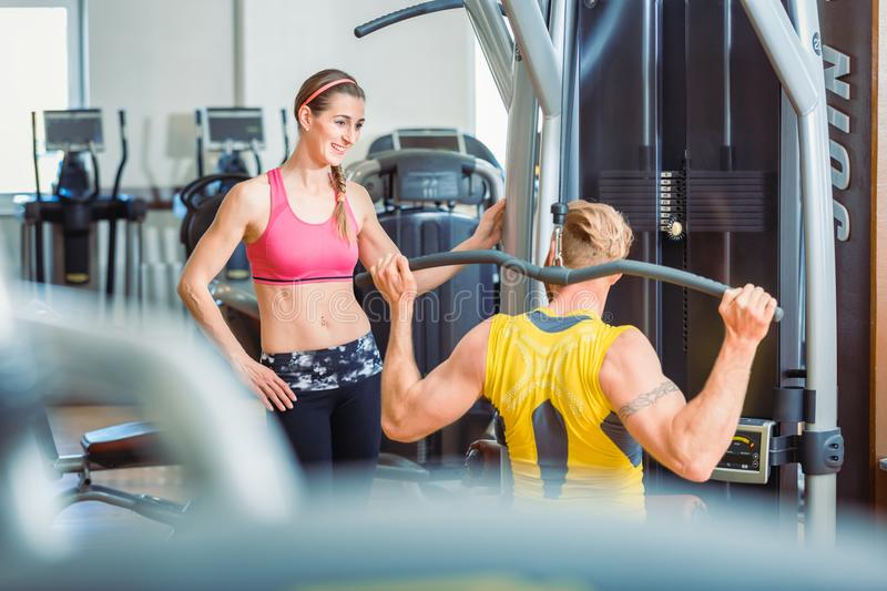 Fit beautiful woman smiling with admiration at a strong man in the gym. Fit beautiful women smiling with admiration at a strong men exercising overhead lat stock photography