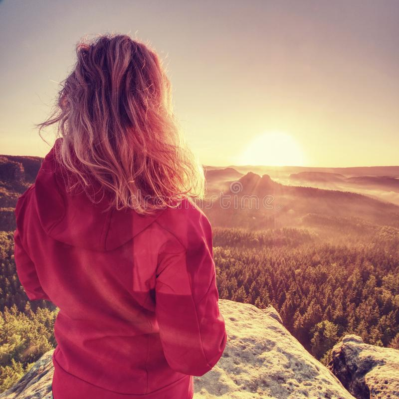 Fit body blond hair woman on the top of the high rock stock photos