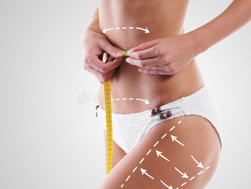 Fit body of a young and woman. Thin woman measuring her torso with scale having arrows on hips. Plastic surgery concept royalty free stock image