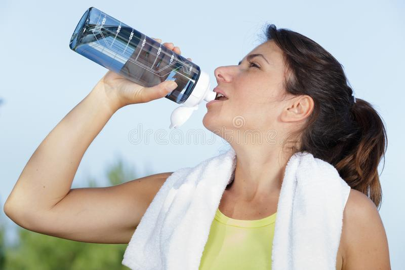 Fit brown hair drinking from water bottle royalty free stock photo