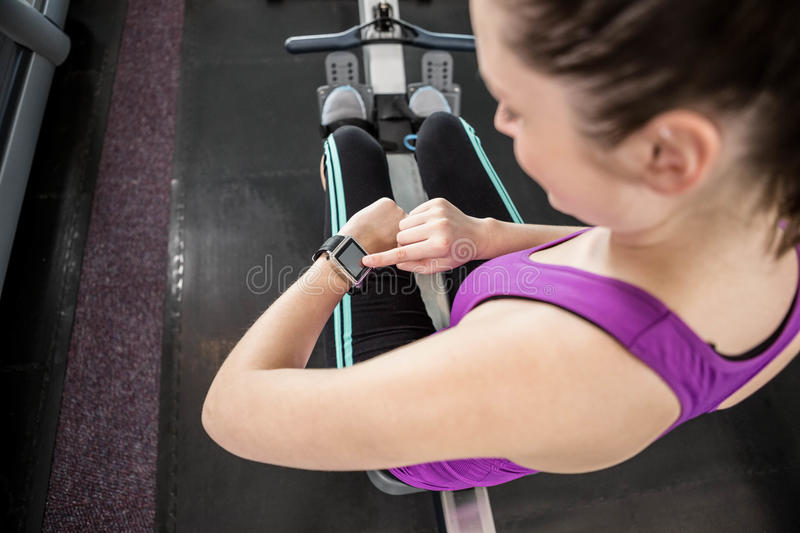 Fit brunette on drawing machine looking at smartwatch royalty free stock photos