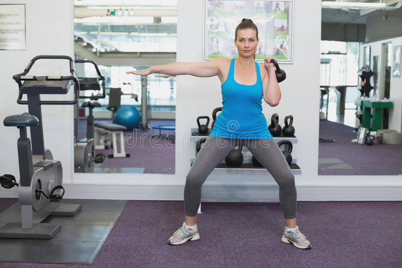Fit brunette working out with kettlebell stock images